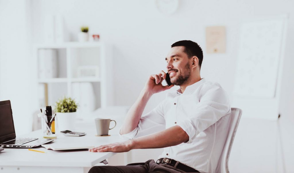 attractive businessman sitting down at desk on phone